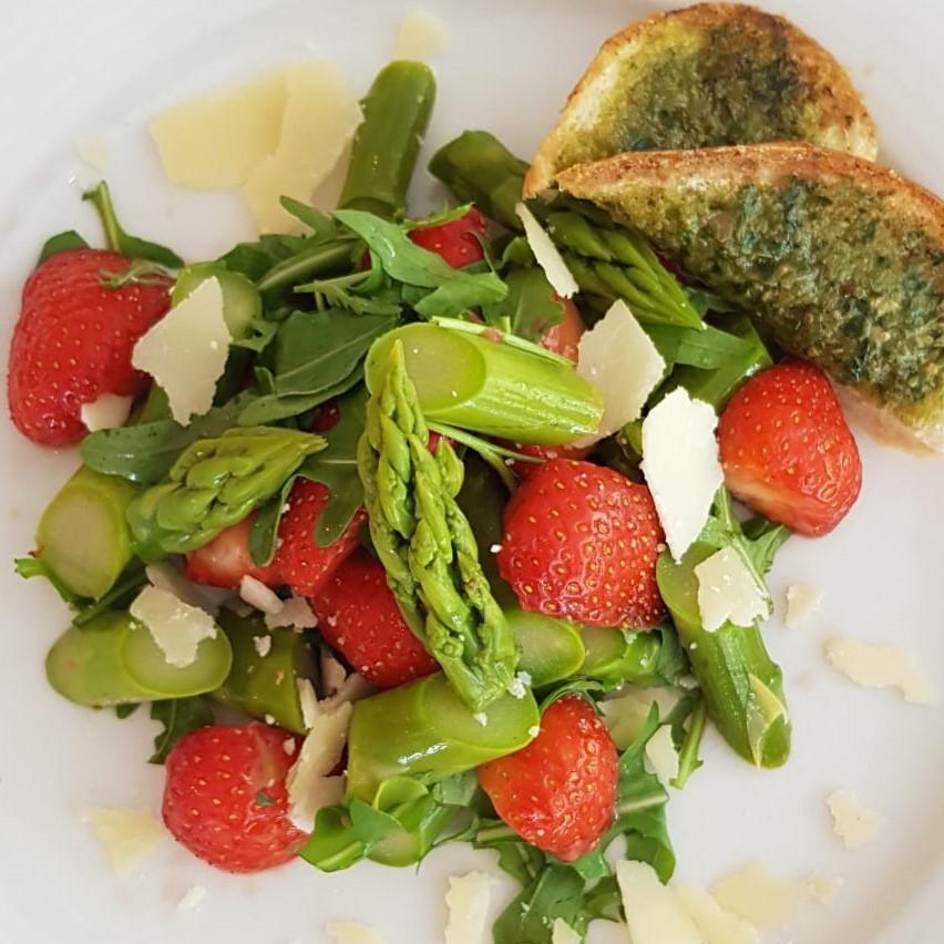Juni 2019: Salat von grünem Spargel mit Rucola, Erdbeeren und Parmesan, dazu zwei Stücke selbstgemachtes Kräuterbaguette
